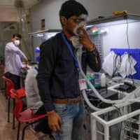 AgVa employee Vaibhav Gupta demonstrates using a ventilator at a research and development center in Noida in Uttar Pradesh state on March 25. | AFP-JIJI