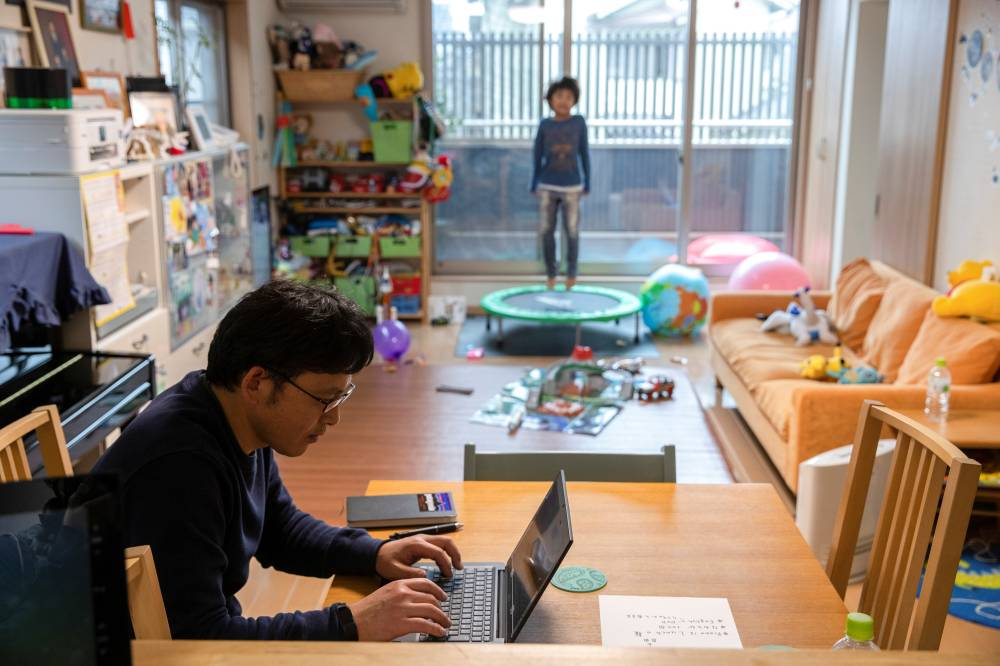Koji Ishii, 49, works as his son Leo, grounded by school closures this month, plays at their house in Chiba Prefecture in March. | REUTERS
