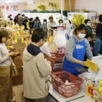 Stocking up: Shoppers buy food at a supermarket in Tokyo after  Gov. Yuriko Koike asked citizens to refrain from going outside for nonessential reasons amid a sharp increase in the number of coronavirus infections in the capital.  | KYODO