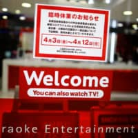 A notice of temporary closure is displayed Friday at the entrance of a karaoke booth building after Tokyo Gov. Yuriko Koike urged residents of the capital to stay indoors in a bid to keep the new coronavirus from spreading. | REUTERS