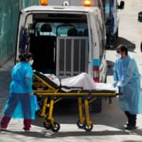 Ambulance workers push a stretcher with a patient from a nursing home during the coronavirus outbreak near Madrid on Thursday. | REUTERS