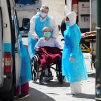 Ambulance workers push a wheelchair with a patient at a nursing home during the coronavirus disease outbreak near Madrid on Thursday.  | REUTERS