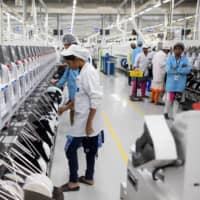 Employees work on an assembly line at a mobile phone plant operated by Rising Stars Mobile India Pvt., a unit of Foxconn Technology Co., in Sriperumbudur, Tamil Nadu, India, in July last year.  | BLOOMBERG