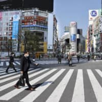 A scramble intersection in Tokyo's Shibuya district is nearly empty for a Saturday. The metropolitan government asked citizens to refrain from leaving their homes this weekend to prevent the further spread of the new coronavirus.   KYODO