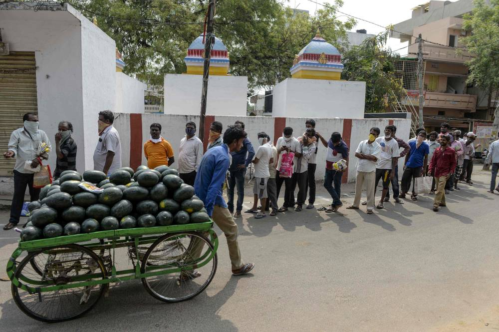 A watermelon vendor walks past people queuing as they wait to receive free rice distributed at a government civil supply store during a government-imposed nationwide lockdown as a preventive measure against the COVID-19 coronavirus, in Hyderabad on April 3, 2020. | AFP-JIJI