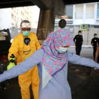 A worker sprays disinfectant on a woman during a lockdown in Kuala Lumpur on April 1. | REUTERS