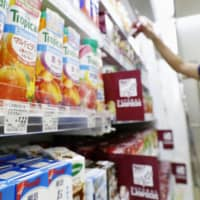 Stocking up: A convenience store worker checks merchandise at a shop in Japan. Customer spending helped boost sales at the nation's convenience stores as people prepared to stay home more because of the spread of COVID-19. | KYODO