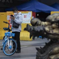 A resident checks his phone near a sealed off community in Wuhan, China, on Sunday.   AP