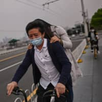 A couple ride a bicycle over Wuhan Bridge on Sunday.   AFP-JIJI