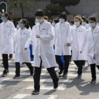 Medical workers from Beijing walk near a park in Wuhan during a day off.   AP