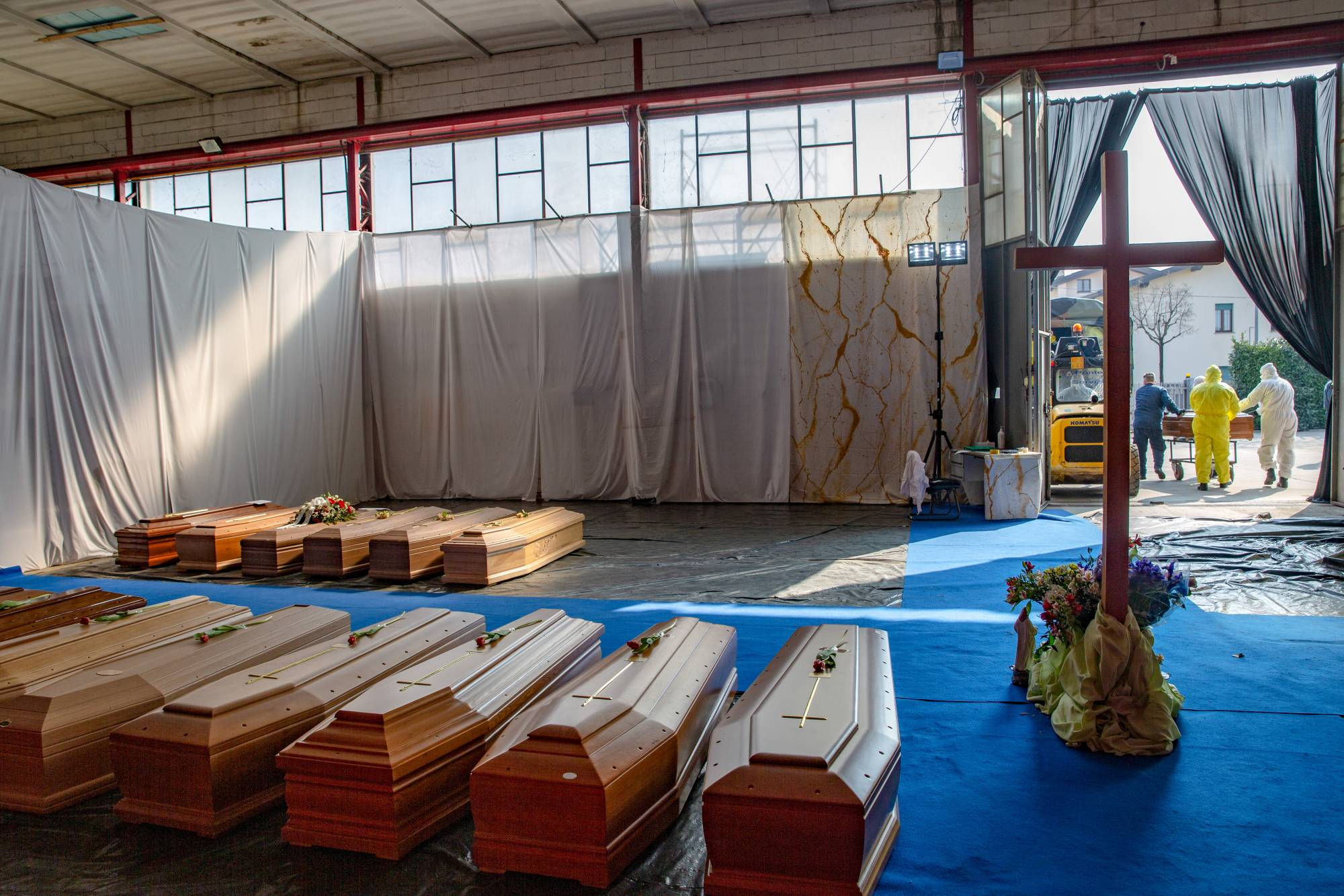 A cross stands among coffins for victims of the coronavirus in a repurposed warehouse in Ponte San Pietro, near Bergamo, Northen Italy, on Saturday. | BLOOMBERG
