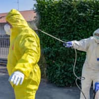 A member of a civil protection team sprays a colleague with sanitizer in Ponte San Pietro, near Bergamo, on Saturday. | BLOOMBERG