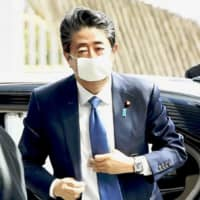 Prime Minister Shinzo Abe arrives at his office in Tokyo on Monday morning. The government is set to announce an emergency economic package Tuesday. | KYODO