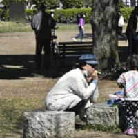A mother and daughter play in a park in the city of Saitama last month. Extra time spent with family members could lead to more acts of violence, experts have warned. | KYODO