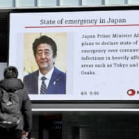 People walk by a big screen in the Akihabara district of Tokyo on Monday broadcasting news that Prime Minister Shinzo Abe is set to declare a state of emergency over the growing spread of COVID-19 in Japan. | KYODO