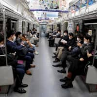 People wearing face masks amid concerns over the spread of the COVID-19 coronavirus, commute on a train in Tokyo on Monday.  | AFP-JIJI