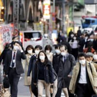 People wearing masks walk in the Shimbashi district of Tokyo on Monday. | KYODO