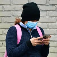 A woman wears a mask while checking her cellphone in Los Angeles. | AFP-JIJI