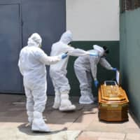 Soldiers wearing biohazard suits to protect themselves from COVID-19 pick up a coffin containing a body left outside a house in Guayaquil, Ecuador, on Monday. | AP