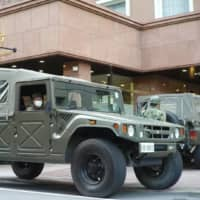 Self-Defense Forces vehicles arrive at a Toyoko Inn in Tokyo on Tuesday to assist the hotel in accepting COVID-19 patients. | RYUSEI TAKAHASHI