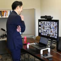 Satoshi Yoshii, professor at Nagoya University of Commerce and Business, interacts with his students during an online lecture Monday. | KYODO