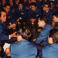 Kazuo Inamori discusses his ideas with workers of Kyocera Corp. at a party after announcing the company's management policy in January 1982. | INAMORI LIBRARY, KYOCERA CORP.