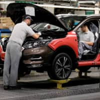 Workers are seen on the production line at Nissan's car plant in Sunderland, England. | REUTERS
