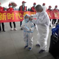 Travelers wearing masks and suits to protect against the spread of new coronavirus walk past people holding a celebratory banner at Wuhan Tianhe International Airport on Wednesday. Within hours of China lifting an 11-week lockdown on the central city, tens of thousands people left the city by train and plane alone, according to local media reports.  | AP