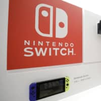 Nintendo Co. Switch game consoles, top, and Switch Lite game consoles are displayed inside the Nintendo Tokyo store. | BLOOMBERG
