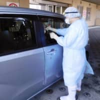 An official demonstrates how doctors will perform drive-thru virus testing in the city of Niigata in March. | NIIGATA CITY / VIA KYODO