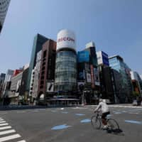 A man riding a bicycle passes a crossing at Tokyo's shopping district Ginza on April 8, 2020, on the first day of a state of emergency due to the COVID-19 coronavirus outbreak. | AFP-JIJI