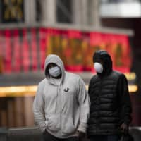 Men wearing masks walk through a rain storm in New York's Times Square on Thursday. | AP