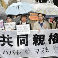 Plaintiffs of a trial questioning the constitutionality of a sole custody system walk to the Tokyo District Court on Nov. 22. | KYODO