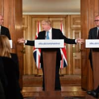 Chief Medical Officer Chris Whitty (left) and Chief Scientific Adviser Patrick Vallance look on as U.K. Prime Minister Boris Johnson speaks about the government's response to the novel coronavirus in London on March 19.   POOL / VIA AFP-JIJI