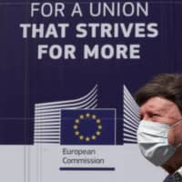 A man walks past the European Commission headquarters in Brussels on Thursday.   REUTERS