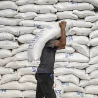 A worker carries a sack of rice inside a National Food Authority warehouse in Valenzuela, Metro Manila, on March 26. | BLOOMBERG