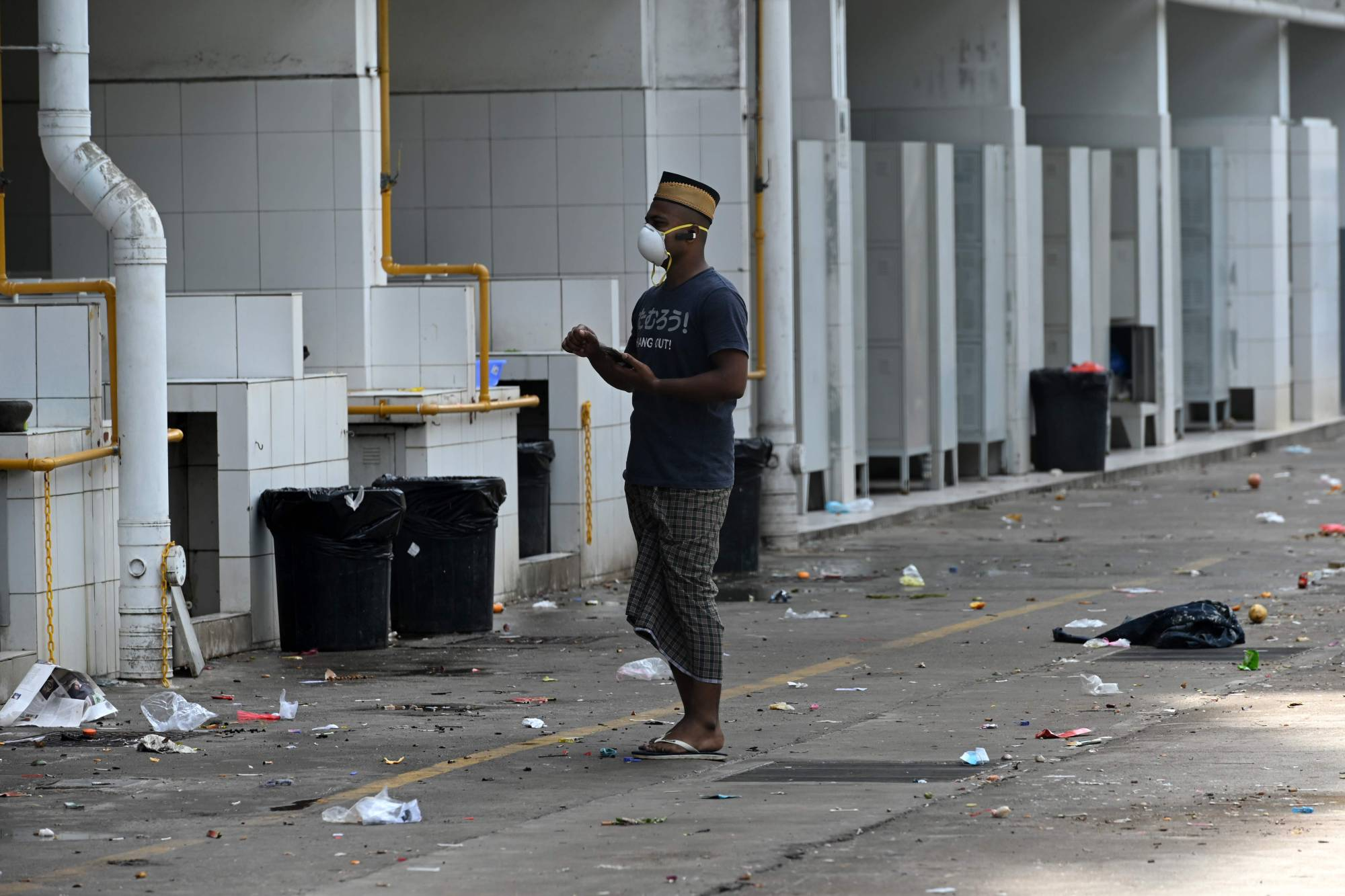 A foreign worker, wearing a face mask as a preventive measure against the spread of COVID-19, stands outside a cooking area of the workers' dormitory in Singapore on Wednesday. | AFP-JIJI
