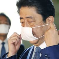 Abe with mask: Prime Minister Shinzo Abe takes his face mask off before meeting the media.  | KYODO
