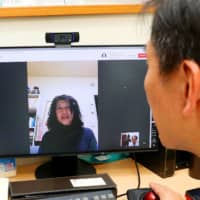 Naomi Kitamura (on screen), a patient with high blood pressure, has an online consultation with a doctor at a Tokyo hospital in January 2018. | KYODO