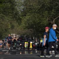 People take advantage of minimal traffic as they run, walk, jog and cycle down East Capitol Street in Washington on Monday. | REUTERS