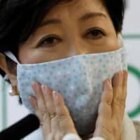 Tokyo Gov. Yuriko Koike holds a news conference Friday at City Hall in Shinjuku Ward to announce emergency measures for the coronavirus pandemic. | REUTERS