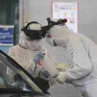Medical staff wearing protective suits take samples from a person with suspected symptoms of the new coronavirus at a drive-thru test facility in Goyang, South Korea, last month. Officials on Friday reported that 91 patients in the country thought to have recovered from the new coronavirus had tested positive again. | AP