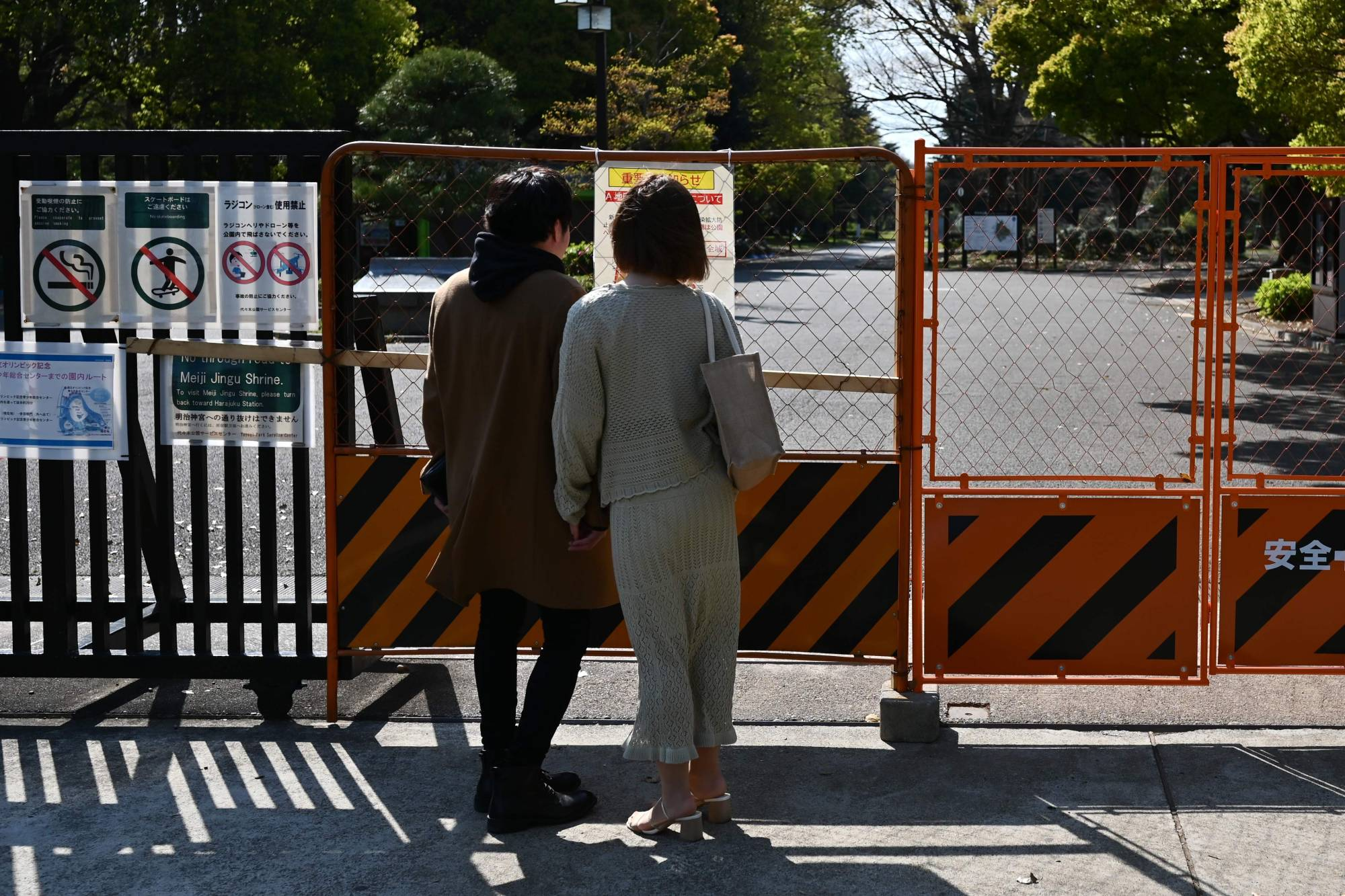 A couple stand before the entrance to Tokyo's Yoyogi Park on Saturday after a monthlong state of emergency was declared in the capital and six other prefectures over a spike in coronavirus cases. | AFP-JIJI
