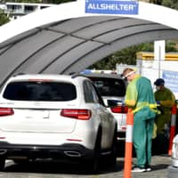 Medics perform COVID-19 tests at a drive-thru testing center on Bondi Beach in Sydney on Saturday. | AFP-JIJI