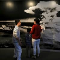 A family looks at a photograph of the A-bomb's mushroom cloud at the Hiroshima Peace Memorial Museum in March 2015. | REUTERS