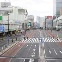 A near-deserted street in front of Shinjuku Station in central Tokyo on Sunday afternoon. | KYODO
