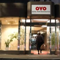 A person enters an Oyo hotel, operated by Oyo Hotels Japan G.K., in Tokyo in January. | BLOOMBERG
