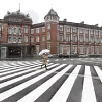 A pedestrian walks across a street in front of Tokyo Station Monday morning. The capital remains in a state of emergency as Japan attempts to contain further spread of the new coronavirus. | KYODO