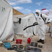 A sanitation worker disinfects a camp for displaced Syrians next to the Idlib municipal stadium in the northwestern Syrian city on Thursday. | AFP-JIJI