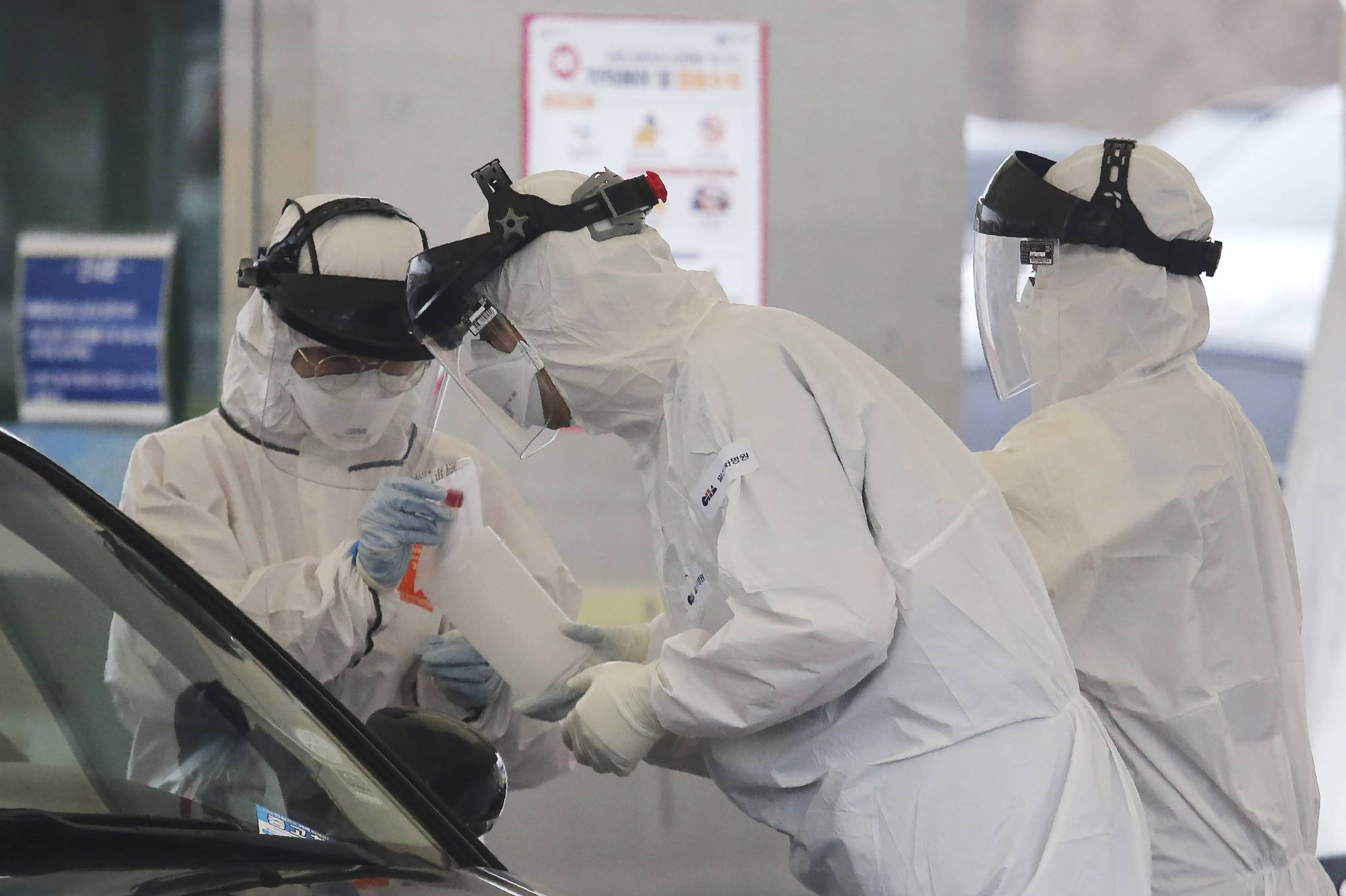 Medical staff wearing protective suits take samples from a person with suspected symptoms of the new coronavirus at a drive-thru testing facility in Goyang, South Korea, on March 1. | AP